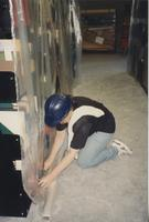 A library worker covers a shelf of books with protective plastic sheeting in the South Building Library during construction, 1994.